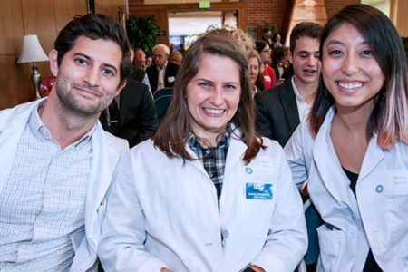 Three students in lab coats smiling.
