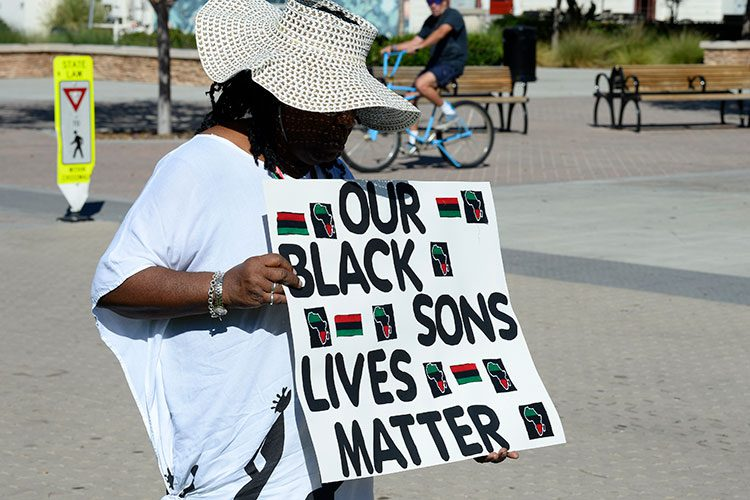 A person holding a sign that reads Our Black Sons' Lives Matter